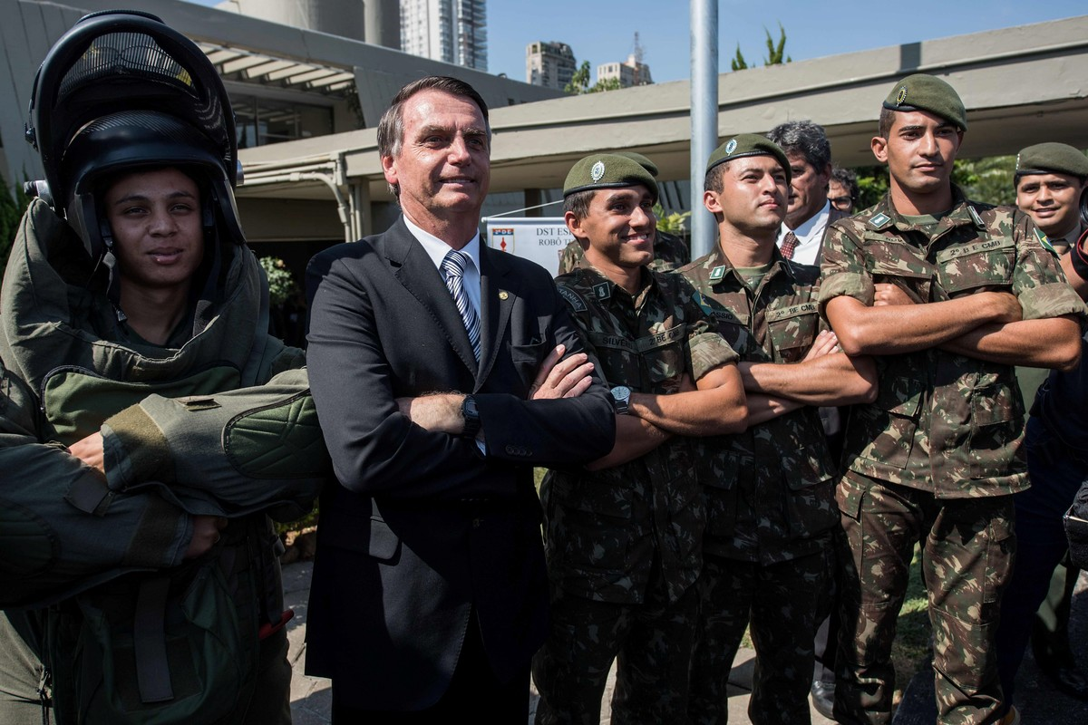Saludo. Jair Bolsonaro posa con militares durante una reciente visita a una base en San Pablo (AFP).